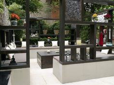 The main focal point of the garden is a large timber structure with integrated shelving and cream travertine topped fixed bench seating around the base. This structure has two open doorways to allow entry from different points in the space, and is ornamented on all sides with a selection of decorative fillers placed within individual alcoves. #pergola #travertine #outdoorroom #insideout