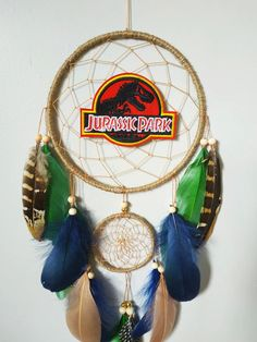 Hang this lovely dream catcher to catch bad dreams while you sleep or bring good vibes into your space. Made with attention and love this dream catcher brings its owners good dreams and positive energy. Materials: ~ metal rings hand wrapped in natural color jute cord ~ tan nylon string ~ wooden beads, gold beads ~ goose and pheasant feathers ~ embroidery Jurassic park dinosaur Dream Catcher Decor, Pheasant Feathers, Birthday Gifts For Boys, Bad Dreams, Dinosaur Birthday, Hand Wrap, Jurassic Park, T Rex, Wooden Beads
