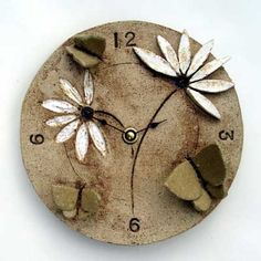 Ceramic wall clock with stylised butterfly and daisy motifs, with a rustic background finish.