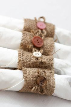 Lot of 50 handmade burlap napkin rings with button and twine bows. Buttons come in a variety of muted earthy colors. Perfect for a rustic country wedding.    Each napkin ring measures about 2 tall and 4.5 around.    Ships out within 1 to 3 days of purchase via USPS with delivery confirmation from Austin TX.