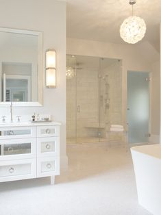 Stunning bathroom with silver beveled mirror over white mirrored washstand accented with nickel ring pull and nickel gooseneck faucet over mini marble tiled floors.