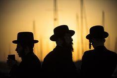 De silhouetten van joodse ultraorthodoxe mannen tijdens het Tashlich ritueel in de stad Ashdod.