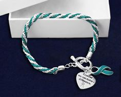 Our wholesale teal ribbon bracelets are perfect for your ovarian cancer fundraising event. Each teal ribbon rope bracelet is perfect for ovarian cancer fundraising. Check out all our teal cancer products in our teal ribbon store. Autism Awareness Bracelet, Ovarian Cancer Awareness, Ribbon Bracelets, Ptsd Awareness, Cervical Cancer, Breast Cancer, Teal Ribbon, Bijoux