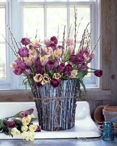 A very pretty pastel flower arrangement that speaks of Spring, but isn't sticky sweet.  I could see using these ingredients; pussy willow branches, peach parrot head tulips and muted mauve tulips and using a lot of different containers to achieve the same effect. The best things inspire us beyond.
