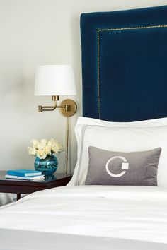 Chic bedroom vignette with shite walls featuring a peacock blue velvet headboard with nailhead trim and white hotel bedding with gray stitching, and monogrammed gray lumbar pillow.