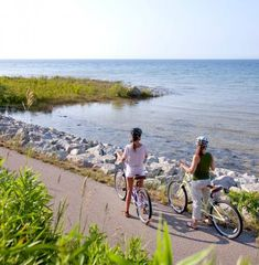 Michigan: The Little Traverse Wheelway  Stunning scenery (and no hills) link Charlevoix, Petoskey and Harbor Springs as you cut through wooded residential areas and hug portions of Lake Michigan shoreline. The best views on the 26-mile trail are south of Petoskey, but you'll also want to make your way north to explore the sand beaches of Petoskey State Park, where teens bake on towels and families play in the waves of Lake Michigan. michigan.org