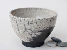 Stilvoller Teegenuss aus Raku Teeschalen  Diese in handschmeichlerisch runder Form mit schönem schwarz-weiß Kontrast zwischen dem glasierten oberen Bereich und dem dunkel eingerauchten unteren...