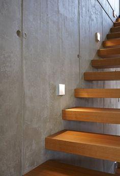 schwebende Treppenstufen an einer Sichtbetonwand : moderner Flur, Diele & Treppenhaus von Marcus Hofbauer Architekt