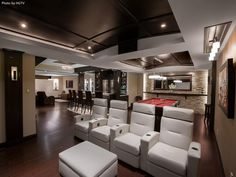Add sleek, white recliners to your theater area in your man cave for a shabby chic design. A pool table and bar area completes the look.