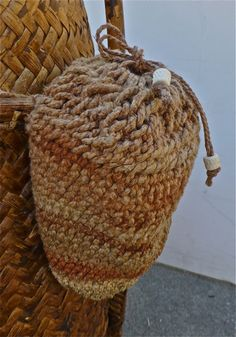 """Looped string bag created from the twisted cordage of seven different plant materials. The 2-ply string was made from (starting from the bottom of the bag) the leaves of New Zealand flax, yucca and chambira palm, along with the bast fibers of hau, stinging nettle, milkweed and dogbane. The bag was attached to a plaited rattan backpack."""
