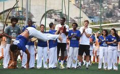Danny Welbeck and Adam Lallana of England applaud as they watch youngsters perform Capoeira during a visit to Complexo Esportivo da Rocinha