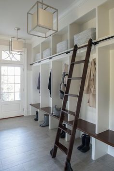 A glass paneled door under a transom window opens to a beautiful white mudroom illuminated by Caged Small Lanterns hung in front of white open mudroom lockers fitted with a dark stained mudroom bench matching a dark stained ladder on wheels, making it easy to reach overhead shelves stuffed with gray baskets.