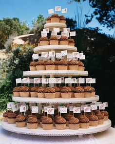 Chocolate-iced cupcakes stood in for wedding cakeat Molly and David's wedding. They were made festive with little flags (created by folding paper around short skewers and securing with double-sided tape); each was printed with a monogram, a palm tree, or polka dots.