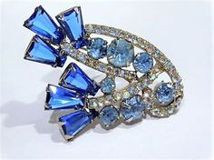 ITEM # 011703 (B-34)   Beautiful verified DeLizza  Elster aka Juliana sapphire blue glass dimensional keystone rhinestone brooch.   Brooch consists of 6 stunning sapphire blue glass faceted glass open back rhinestones in the keystone cut as found in Juliana Jewelry by Ann Pitman, there are 7 varying sizes of aquamarine blue closed foil back faceted glass round rhinestones and 44 small closed foil back faceted glass round accent rhinestones with aurora borealis. All rhinestones have been…