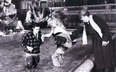 "Federico Fellini helps Anita Ekberg enter in the Fontana di Trevi for shooting a scene from the famous film ""La dolce vita"" - year 1960"
