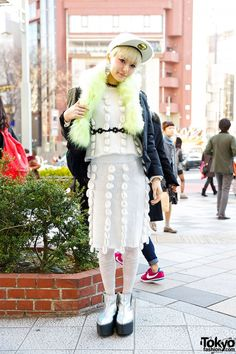 Yuri Nakagawa is a fashion blogger and magazine model whom we often see around Harajuku. This time, her look was short blonde hair and a faux fur cap. Yuri's top and skirt are from lilLilly and they feature textured loops. Her jacket is Fleamadonna, her backpack is Topshop and her silver platform ankle boots are also lilLilly. She is also wearing Chocomoo earrings and a neon faux fur scarf from Moussy. We also noticed her nail art and Chocomoo x Avantgarde Harajuku tights. (Tokyo Fashion…