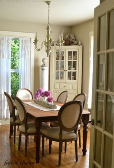 """Dining Room...Chairs from Cost Plus World Market surround Kathleen's dining room table. The ruffled curtains are from Target. """"They allow more light in, and that's important when living in the Pacific Northwest with our dreary winters,"""" she writes on her blog."""