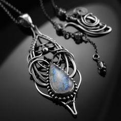 Delikatny, ażurowy, srebrny naszyjnik z pięknym kamieniem księżycowym o intensywnym niebieskim ogniu. Wykonany w całości ręcznie techniką wire-wrapping.  długość wisiora: 70 mm, długość łańcuszka: 88 cm, waga: 17,3 g  materiały: srebro próby 925 oksydowane, przecierane i polerowane, kamień księżycowy, kryształ górski.  BEZPŁATNA PRZESYŁKA. Naszyjnik zostanie wysłany w eleganckim metalowym pudełku.