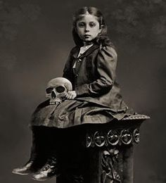 What a strange photo of a little girl holding a skull. Why would anyone pose her with something like that?