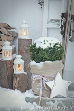 Like to lanterns on tree stumps.  Also love the burlap wrapped around planter with boxwood.