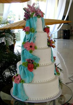 5 layer white wedding cake in buttercream icing with marbled robin egg blue fondant draping and fresh flowers
