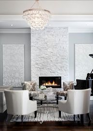 We love the mix of textures, but also the clean, classic lines in this monotone room.  Especially loving how the light gray on either side of the fireplace matches it and completes the look.  Warm and cozy!  #Gray #LivingRoom
