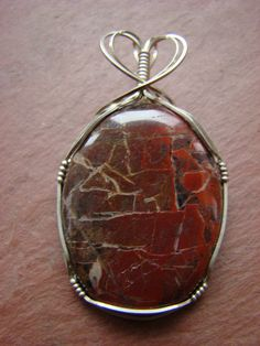 "Pendant. Poppy Jasper Stone wire-wrapped with Argentium Sterling Silver, 2¼"" long. $48.50  Beautiful stone with shades of rusty reds & browns."
