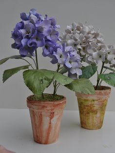 Blue or White Stemmed Hydrangea approx. height is 14 by 10.  Tole leaves with porcelain flowers and pot.