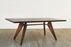 Table démontable Circa 1946 Table de salle à manger à plateau rectangulaire et piétement en bois à quatre pieds en fuselés, réunis par une entretoise en acier tubulaire laqué rouge. Dimensions : H.72 - L. 170 - P. 89 cm Demountable table. Jean Prouvé (1901-1984)