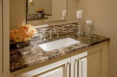 The vanity areas are given the finishing touches with dark emperador marble countertops and a glass and stone blended mosaic backsplash which adds an elegant detail.