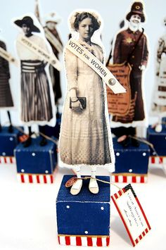 "Great American Suffragette Folk Art Dolls are created from vintage photos transferred onto cotton and gently stuffed. Little Suffies are displayed upon a primitively painted and distressed wooden block. Several designs include a ""Votes For Women"" pure silk ribbon. Other Suffies are decorated with a miniature copy of a Rosette in Suffragette colors of white, purple and green. Petite shoes are hand crafted from paper clay and painted in period style. Small copper tag with 1920 fastens the…"