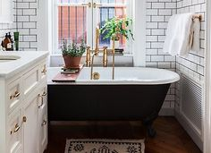 Black grout echoes the coloration of the clawfoot tub and adds texture to this small all-white subway-tiled bath.