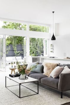 Neutral living room with grey sofa and massive windows. Looks so good with white walls.