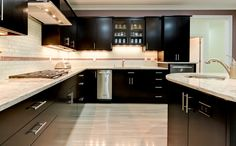 This modern kitchen includes a large center island and desk area that allows for plenty of space to stay organized. Designed and built by Ramage Company.