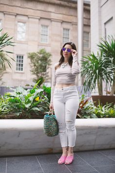 Lifestyle blogger Roxanne of Glass of Glam wearing a striped crop top, Old Navy denim, and a straw bag