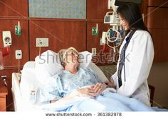 Female Doctor Talks To Senior Female Patient In Hospital Bed - stock photo