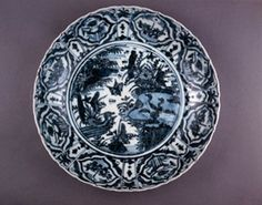 Large Zhangzhou Export Ware porcelain dish of Swatow type, with bracketed rim . Underglaze blue inside with a central roundel featuring ducks and waterfowl in a pond with aquatic plants and a grassy shoreline. Ogival panels around the cavetto alternating with egrets or lotus plants. (Ming dynasty)