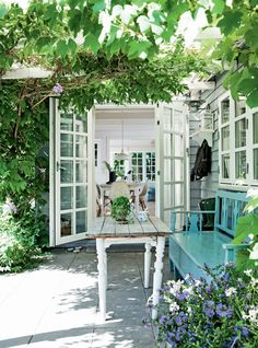 The abundance of plantings, including a trellis covered in wisteria and grapevines, give the feel of the French country.