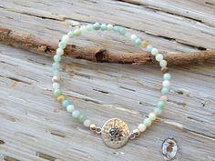 """$48 - AMAZONITE OM BRACELET Amazonite has the ability to block stress and dispel negative energy This understated amazonite bracelet is centered with a beautiful hammered sterling silver om. Stretch bracelet measures 7"""", sized to fit most wrists."""