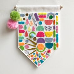 Made from quality cotton fabric and machine stitched on all sides, this banner features hand cut and hand stitched felt pieces. This is a one off, unique banner which is bright, bold and a little quirky! Includes wooden dowel rod and coordinating string for hanging.Banner measurements: W 18cm x L 25cm (approx) Designs and colours may vary slightly to what is shown in picture. Our products are for decorative purposes only - please keep out of reach of children.POSTAGE AND...