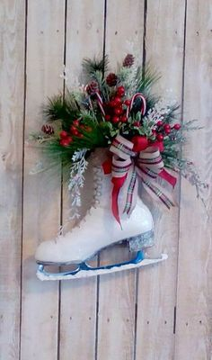 Christmas Ice Skate The details make this ladys vintage ice skate a unique addition to your Christmas decor! Cleaned up and lightly washed with some creamy white paint. Nicely filled with a variety of quality, life like winter pine, pinecones, red berries, and 2 acrylic candy canes. Dressed up with a Plaid and Red burlap Christmas bow and white bell. Finished with white glitter. Lots of cottage charm! Approximately 20 tall - Ready to hang on a door or covered porch. Should be protected…