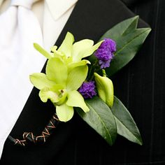 For a groom who's a little on the wild side, this boutonniere of green dendrobium orchids, purple status and leaves wrapped in a black tape with copper wire accents is just the right mixture of funky and fun, Shari Rainka for Tilia Design, tilia.design@gmail.com.