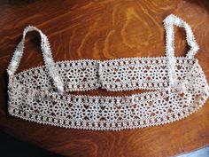 An early tatted edging for the top of a ladies undergarment or bodice. Since tatting is a loose stitch typically of cotton, which tended to stretch easily, the ribbon laced through the shoulder straps would have helped the straps keep their shape.