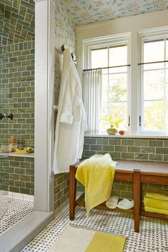 Heated floors, done in basketweave marble tile, and a dry-off station featuring an alder bench with a rush seat keep things cozy in this green bathroom.