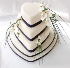 heart shaped wedding cake with ivory icing and navy grosgrain ribbon, sugar calla lillies and white roses