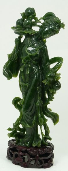 Carved Jade figure depicting Guan Yin holding a platter with peaches and flowers.