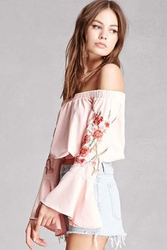 A woven top featuring an elasticized off-the-shoulder neckline, long trumpet sleeves with floral applique, an elasticized hem, and a cropped silhouette. This is an independent brand and not a Forever 21 branded item.