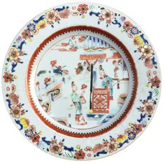 A Chinese famille rose plate decorated with figures. Yongzheng period. Enamelled at the center with two ladies on a terrace and in a building holding a lotus and a fan, and a peony, within a lappet band at the well and a composite flower and a fruit band at the border including prunus, chrysanthemum, pomegranate and finger citrus.