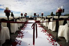 Weißer Teppich mit roten Rosenblättern und große Kerzenständer mit Windlichtern.