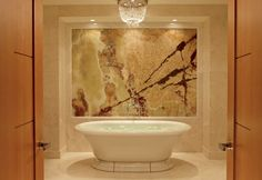 The luxurious free-standing marble soaker tub in The Ritz-Carlton Suite at The Ritz-Carlton, Toronto.